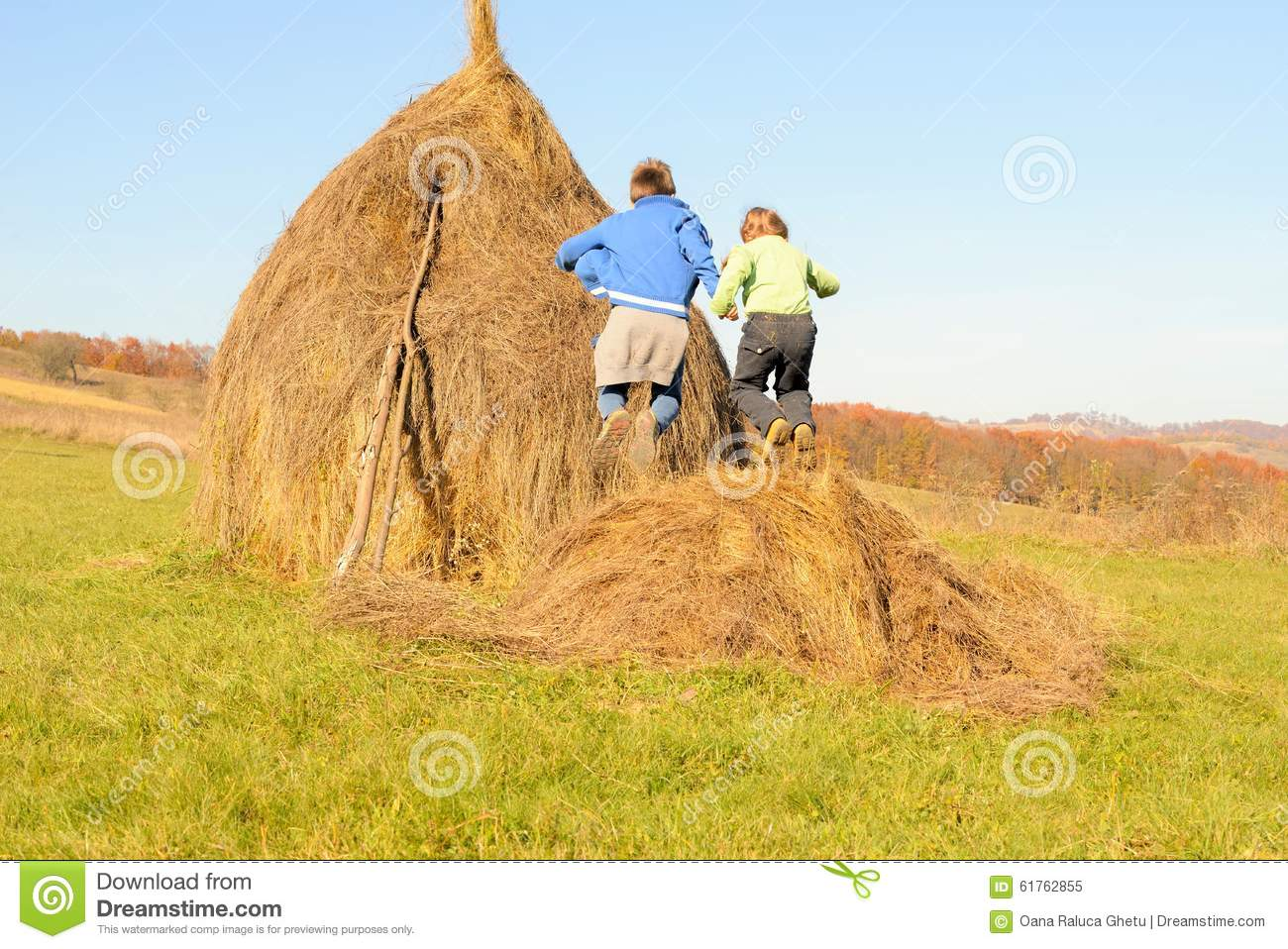 Brother and sister jumping on a haystack