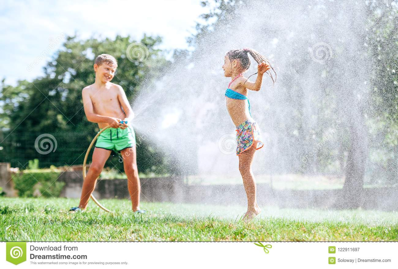 Brother and sister play together with watering hose in garden