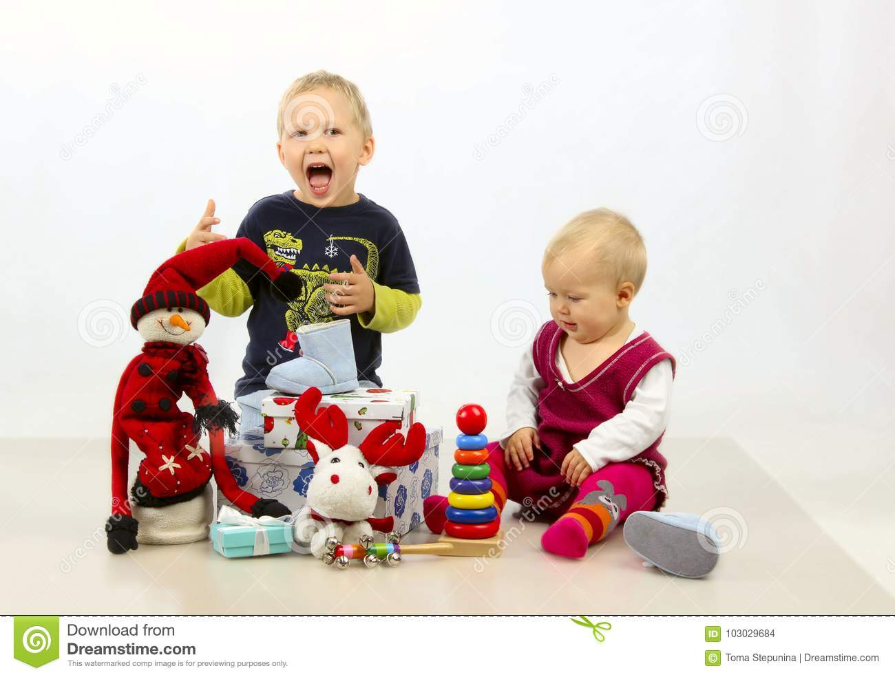 Toys For Siblings : Brother and sister are playing with christmas toys stock