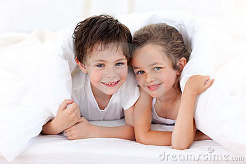 Brother And Sister Playing On Parent S Bed Stock Image