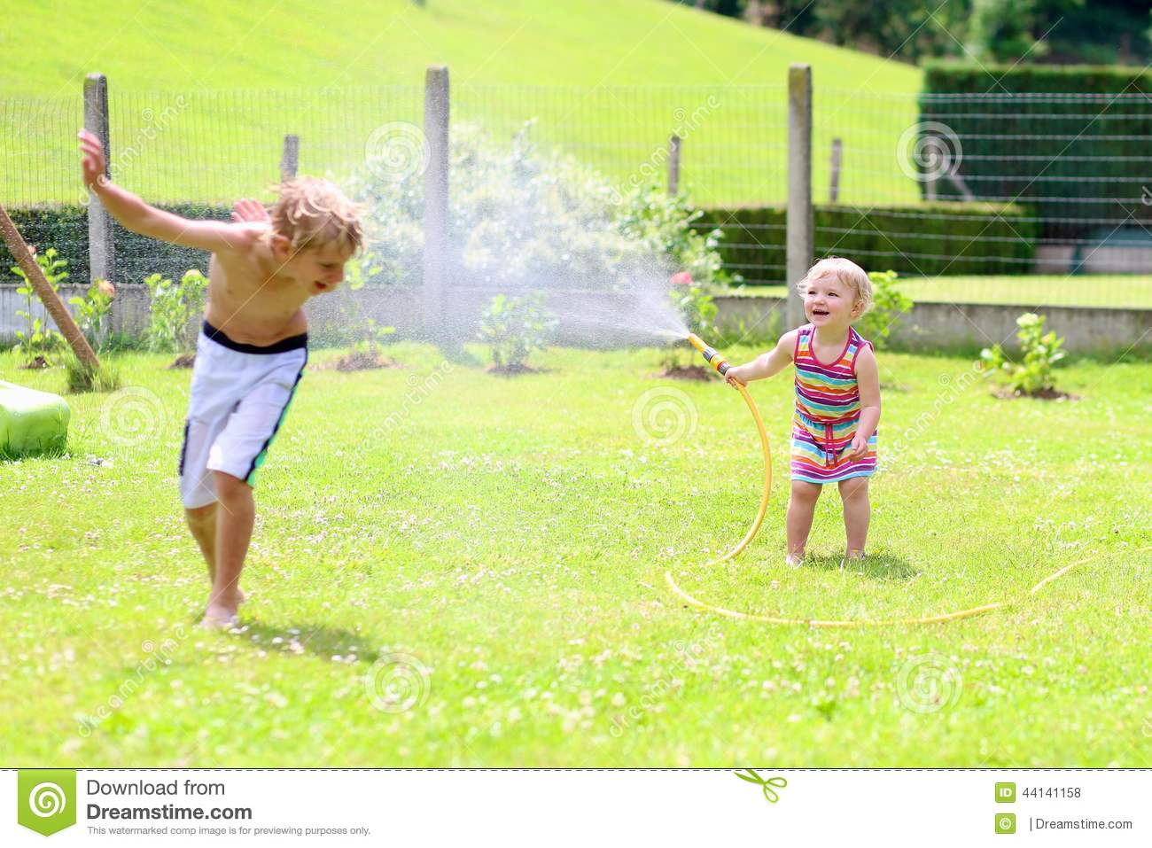 Brother and sister playing with water hose in the garden