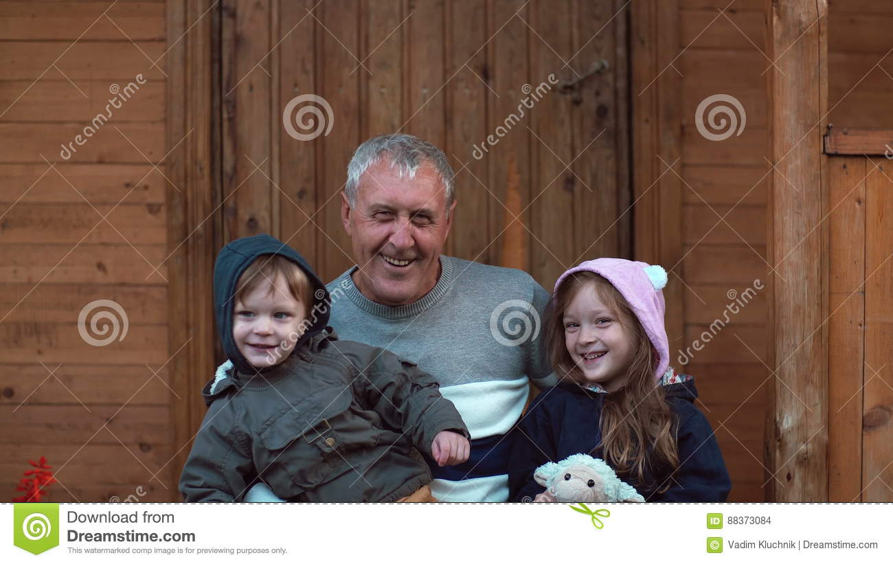 Old men hugs his grandson and granddaughter. Girl kiss the grandfather.  Cute little boy and girl spending time with family, smiling and laughing. 4K