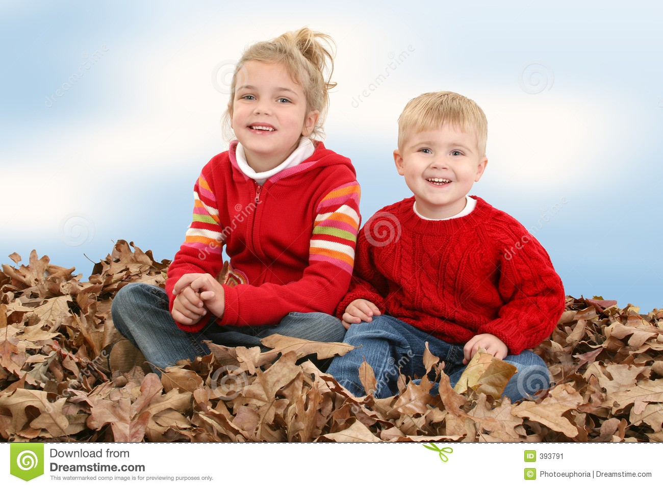 Brother and Sister Sitting in Pile of Leaves