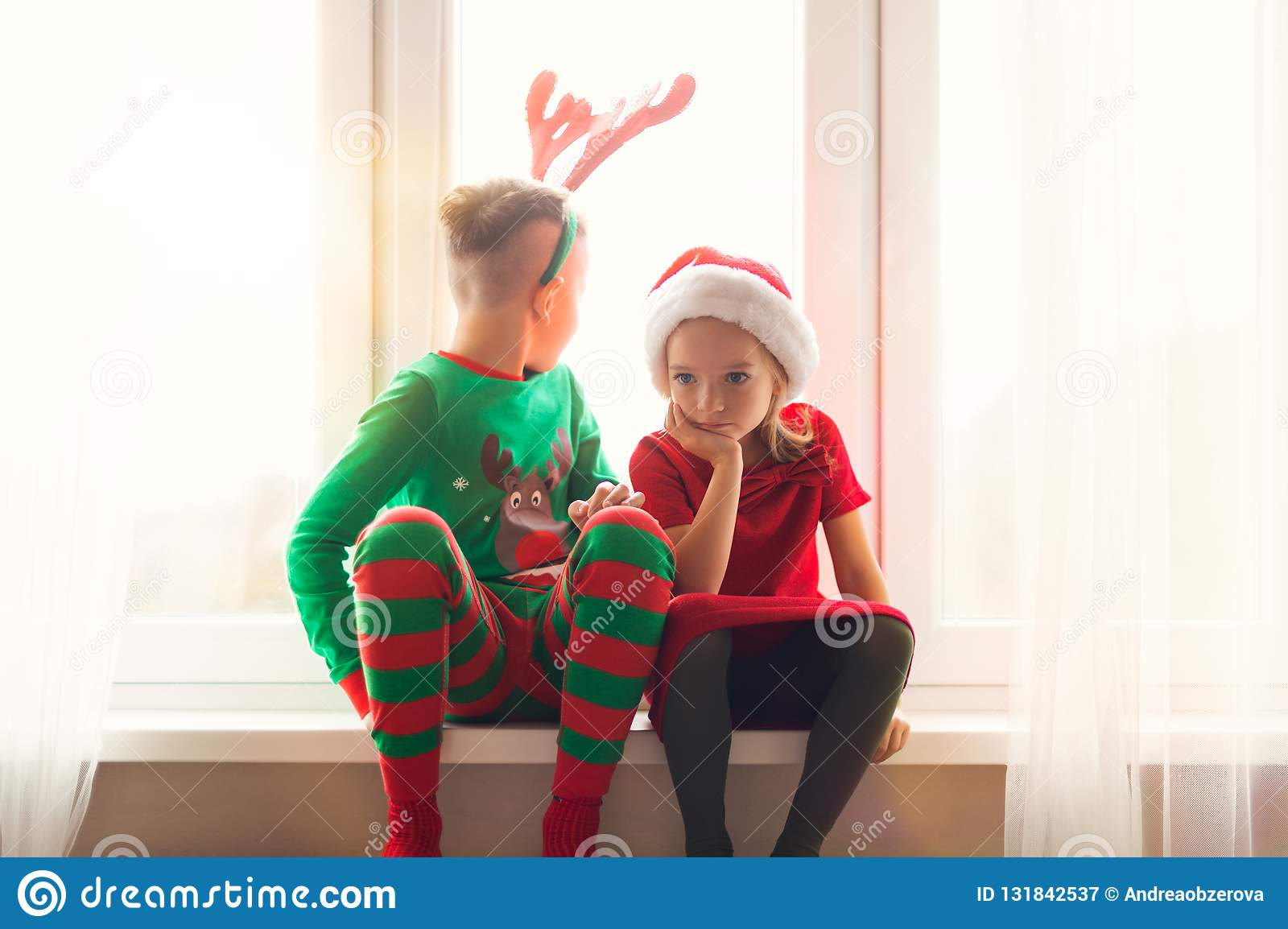 Brother and sister sitting restless on window sill at christmas time, looking out the window, anxiously waiting for Santa Claus.