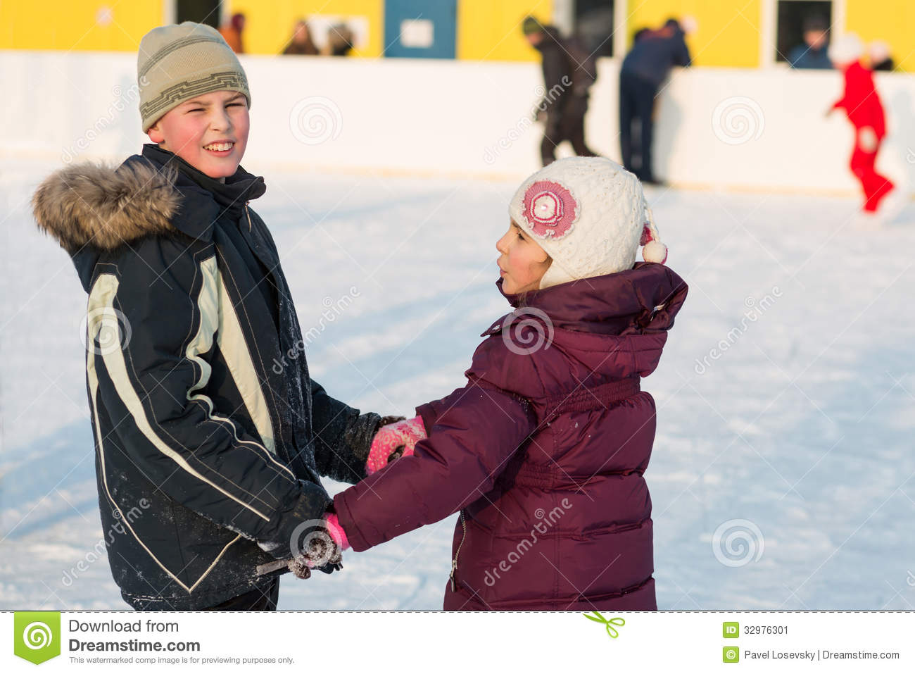 Brother and sister skating on rink hand in hand