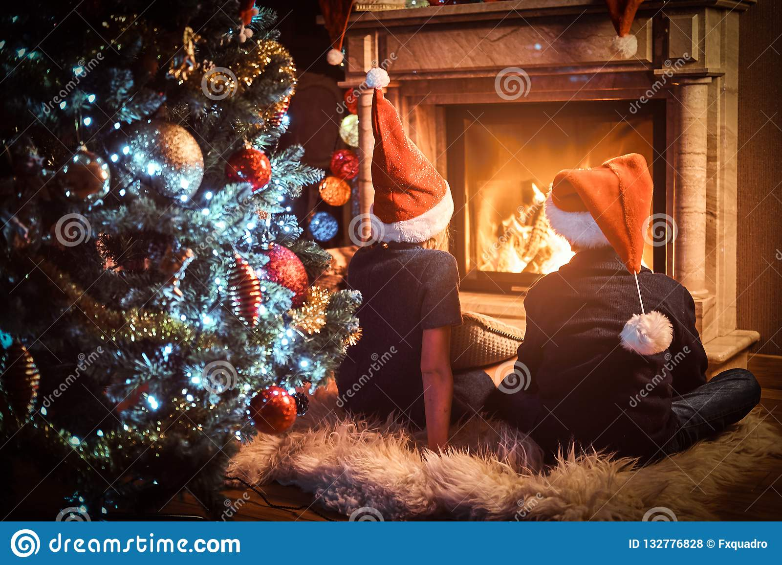 Back view, brother and sister wearing Santa`s hats warming next to a fireplace in a living room decorated for Christmas.