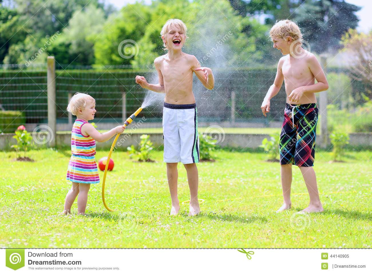 Brothers and sister playing with water hose in the garden