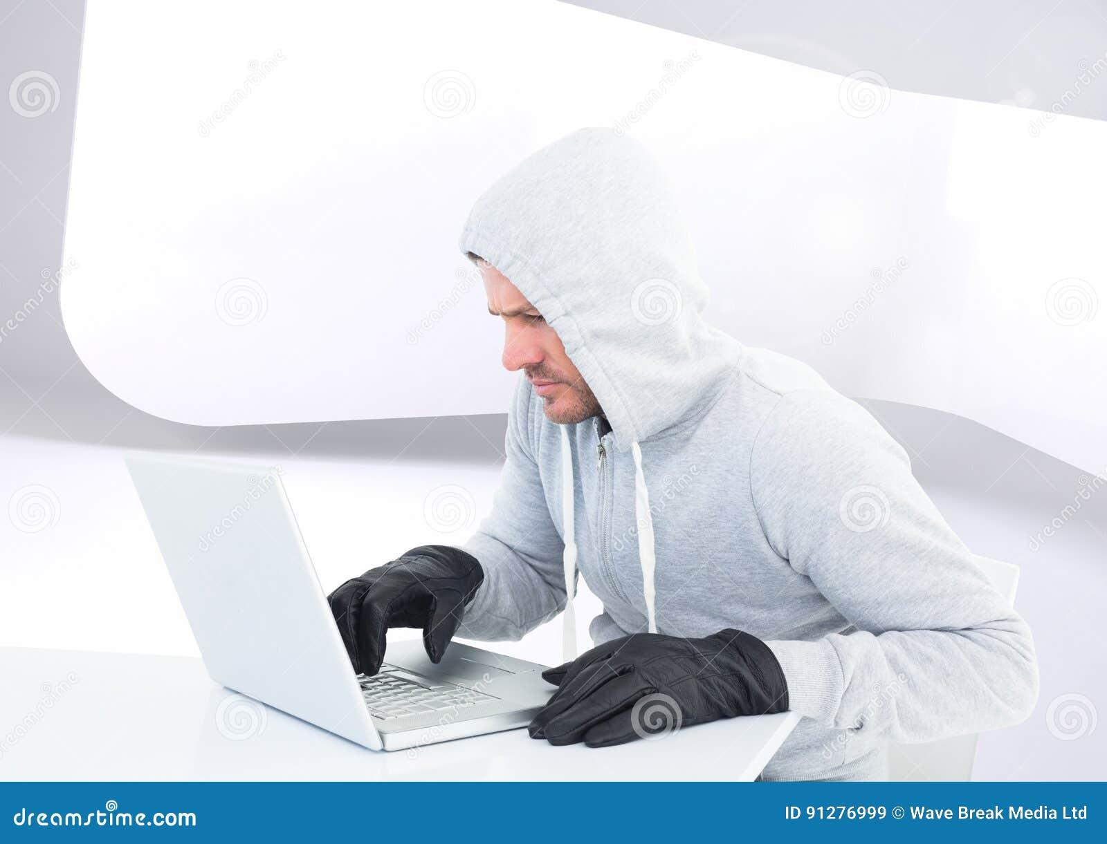 Brottslig man i huv på bärbara datorn framme av modern bakgrund