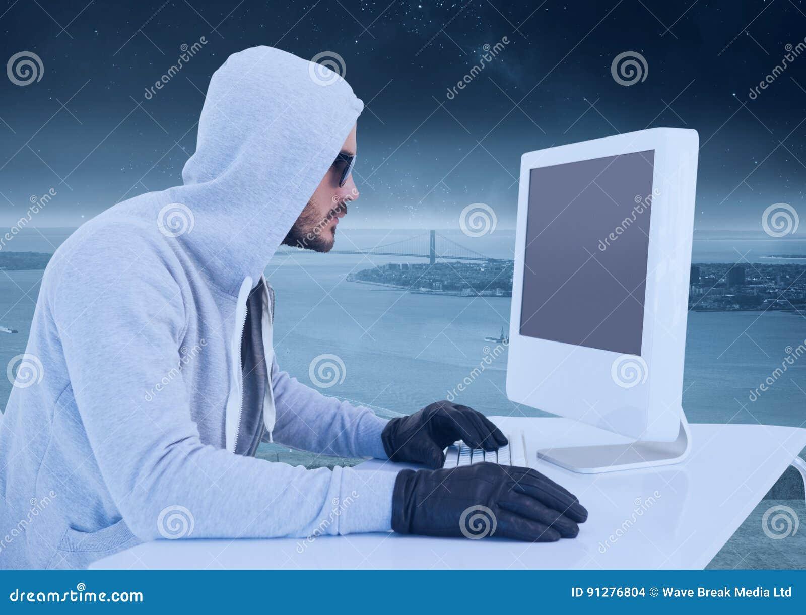 Brottslig man i huv på datoren framme av landskapet
