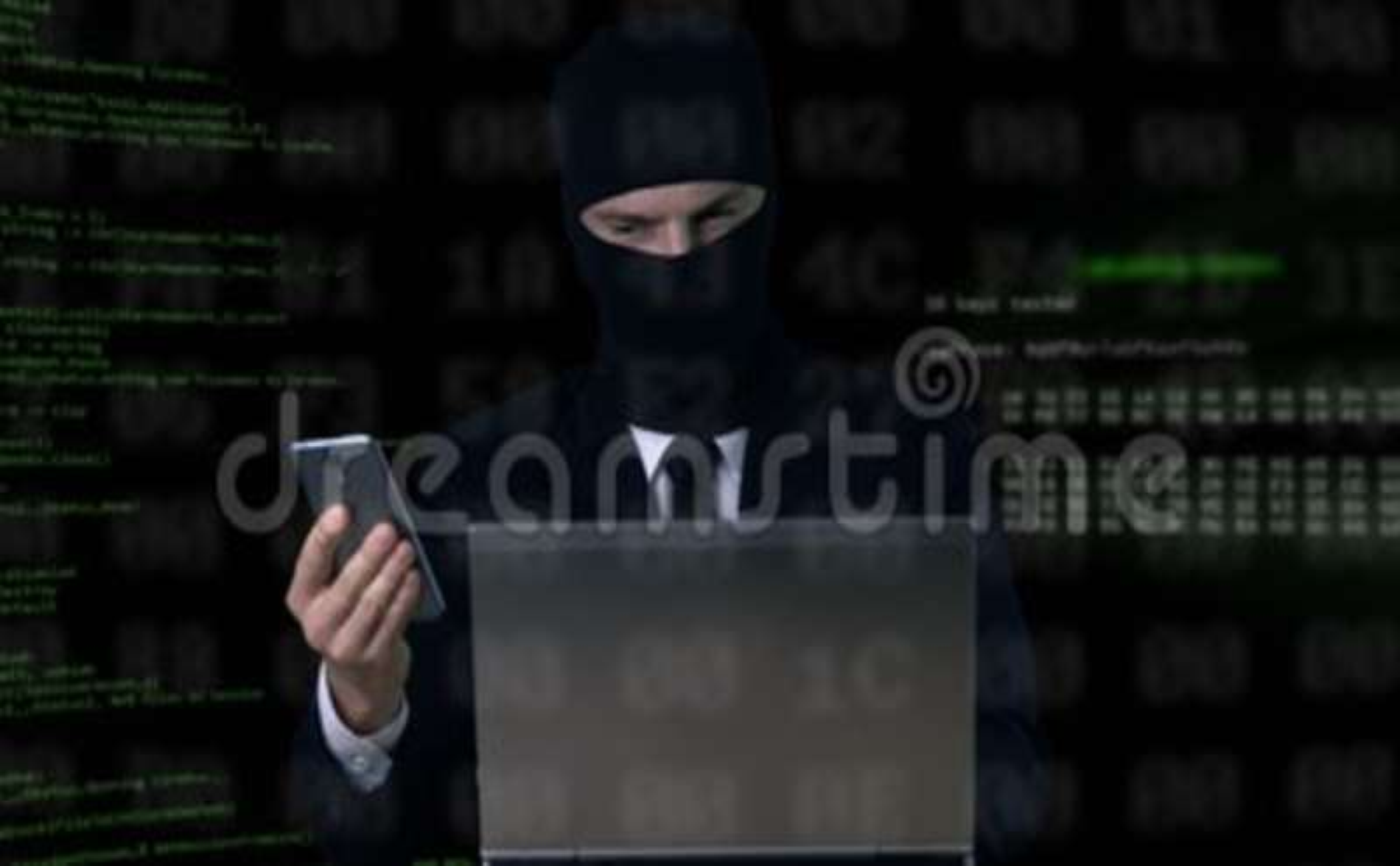 Brottsling i dräkt och balaclava som bryter säkerhetskod genom att använda bärbara datorn och telefonen arkivfilmer