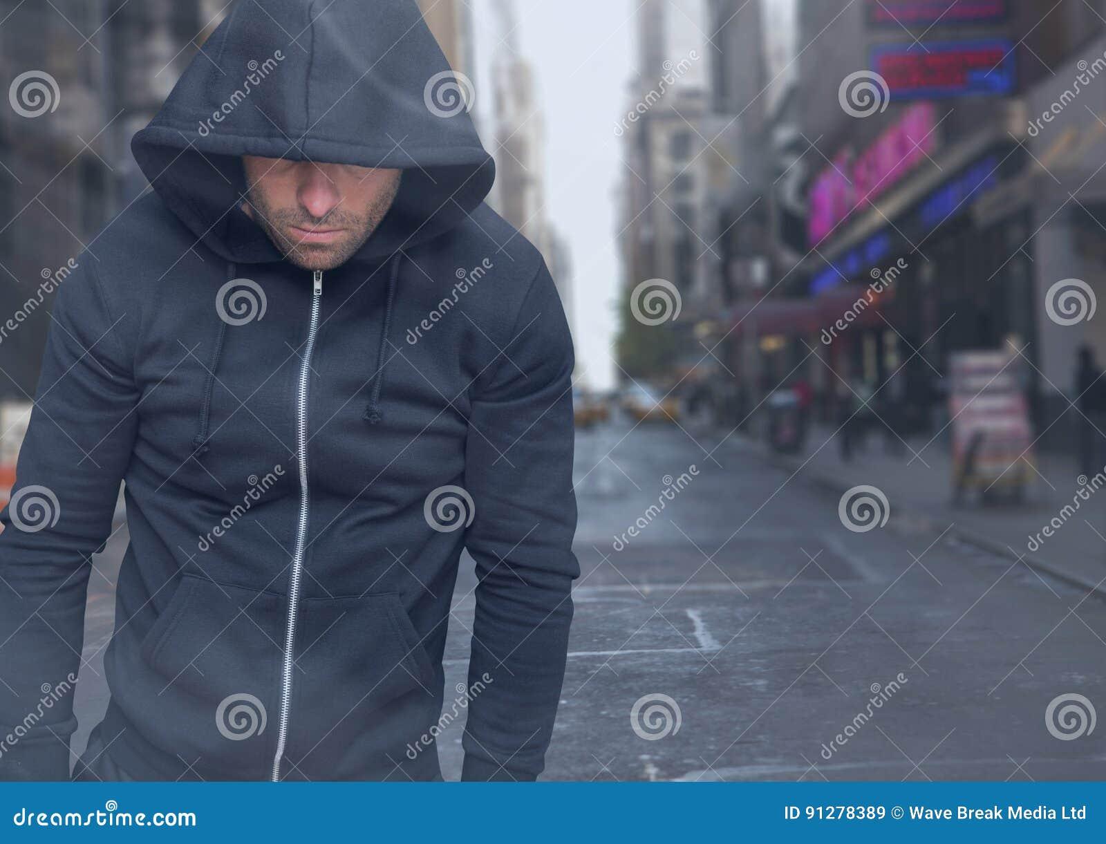 Brottsling i huv framme av stadsgatan