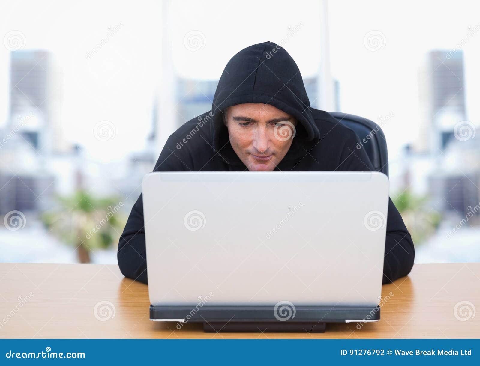 Brottsling i huv på bärbara datorn vid fönster