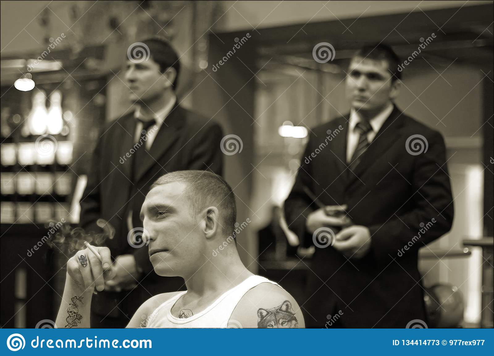 Brovary, Ukraine, 22.02.2006 Man in prison tattoos is smoking. Two his guards stand behind