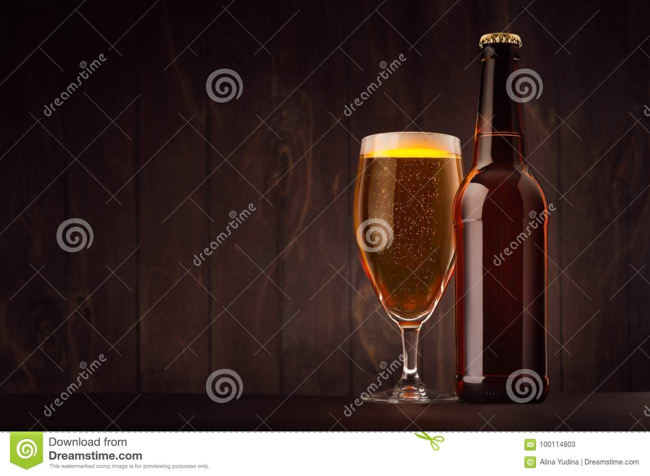 Brown beer bottle and glass tulip with golden lager on dark wood board, copy space, mock up.