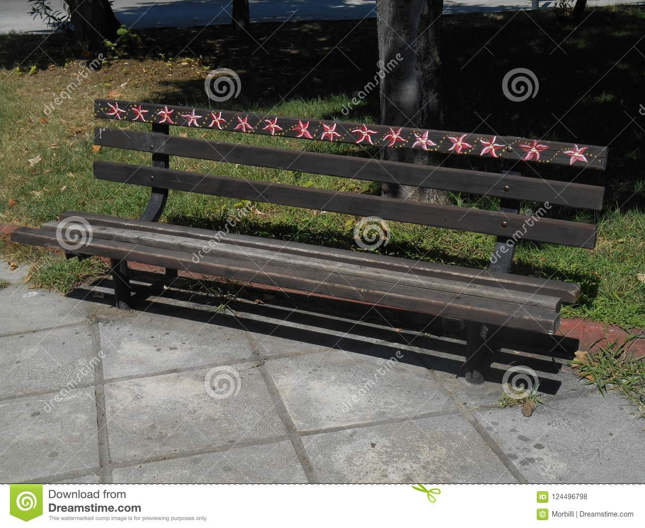 Brown bench painted in little red and white seashells
