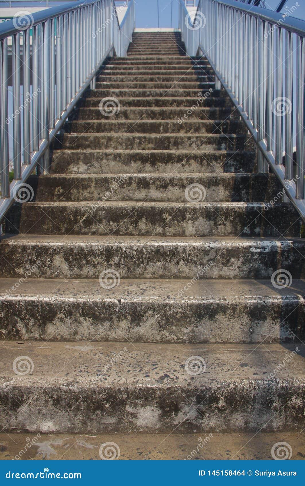 Brown betonuje schodki z stal nierdzewna poręczami, błyszczący kolory