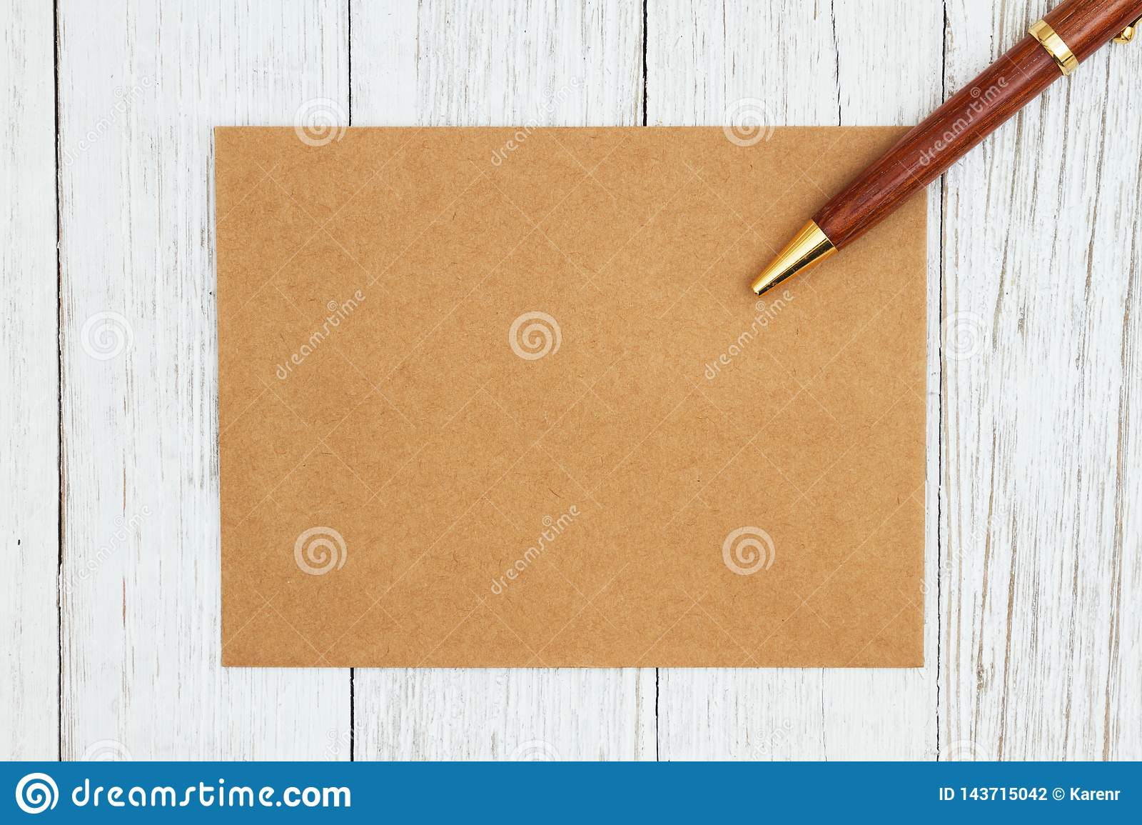 brown blank greeting card with pen on weathered whitewash