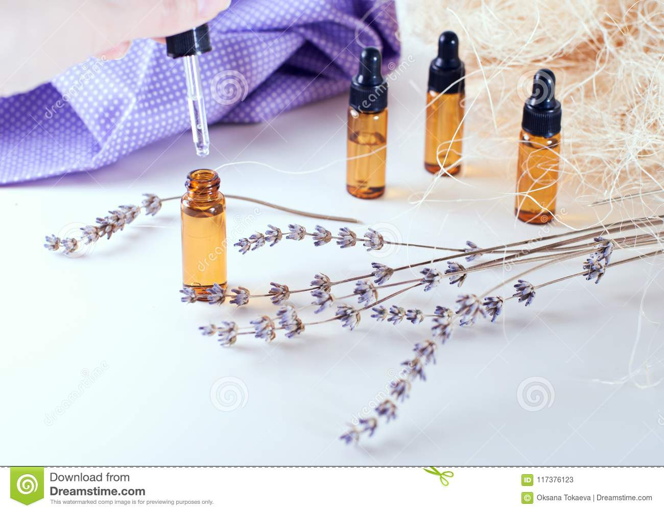 Brown bottles of essential oil with dry lavender