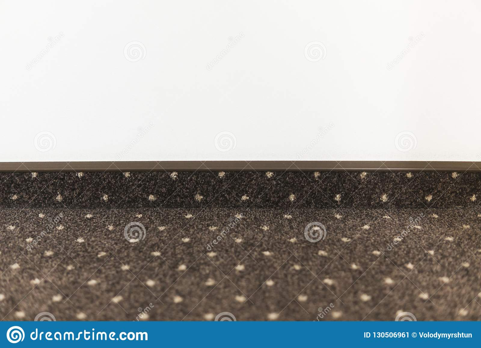 Brown carpet floor with a white dots with a carpet baseboard on a white wall.