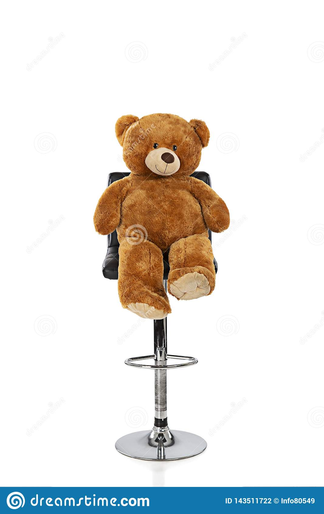 Teddy bear sitting on a stool with a white background