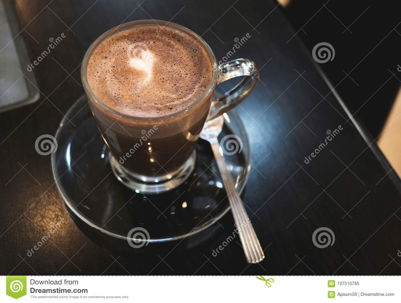 Brown cocoa in coffee cup with white heart shape on black wooden table background