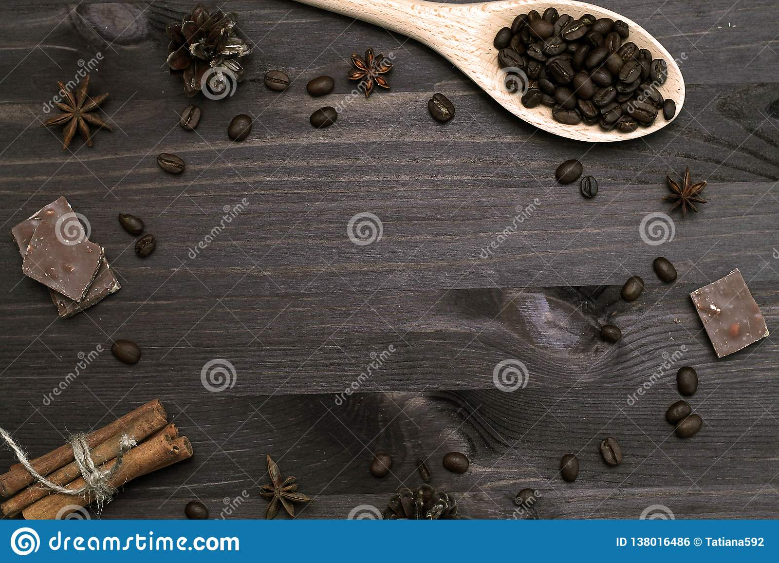 Coffee beans and cinnamon sticks on wooden background