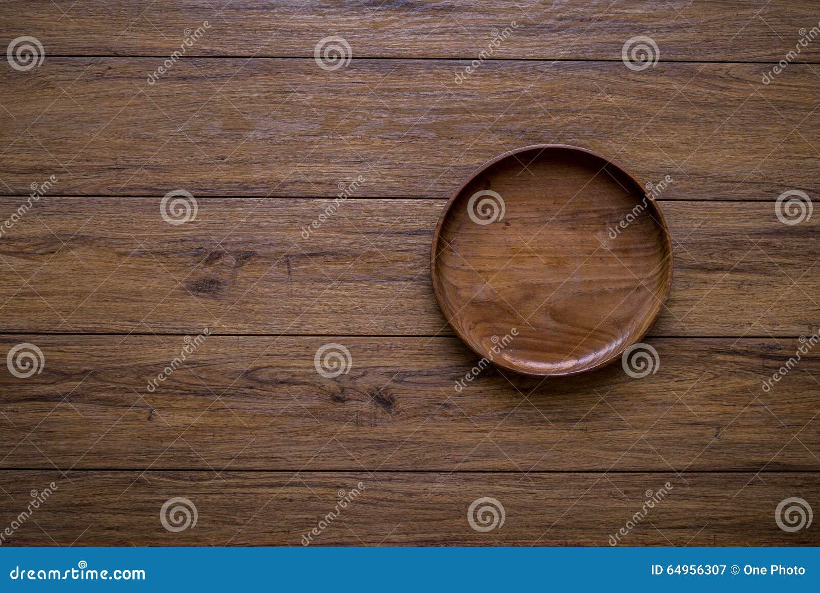 Brown drewniany talerz na nieociosanym stołowym zbliżeniu horyzontalny wierzchołek