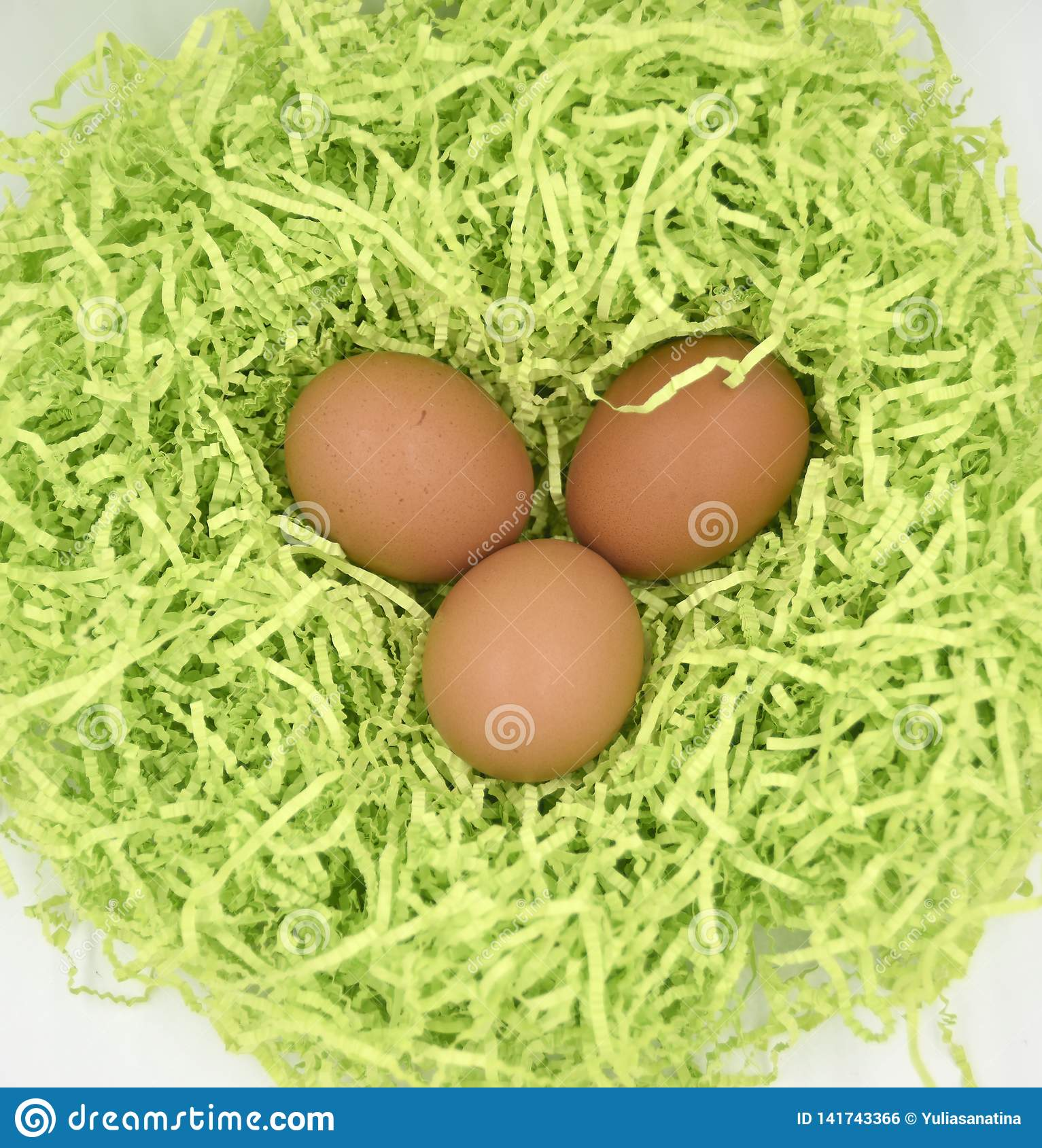 Brown eggs in the green nest made of crumpled paper ob the white background