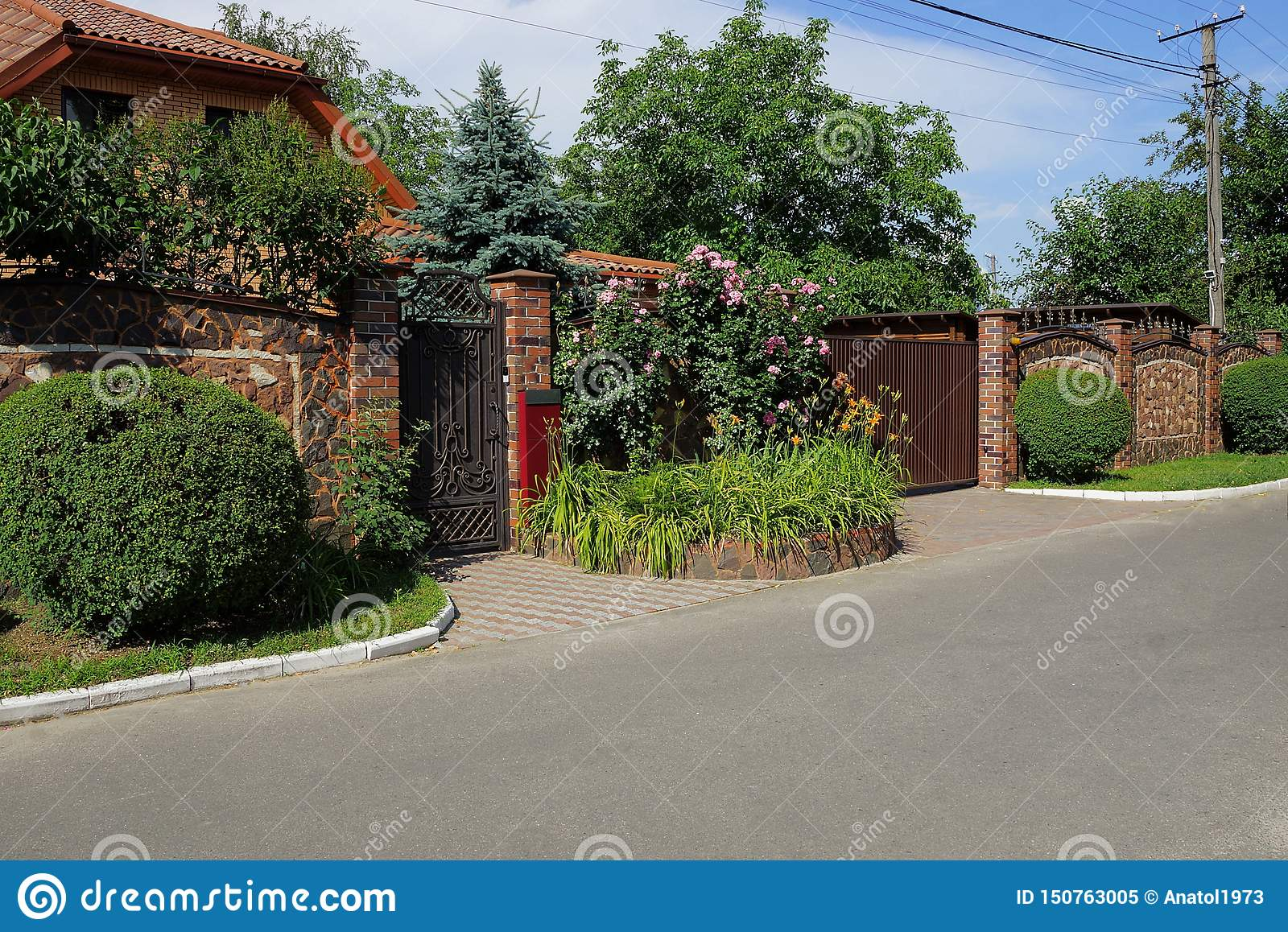 Brown Fence And Gate On The Street With Green Vegetation And Flower Bed Stock Image Image Of Modern Green 150763005