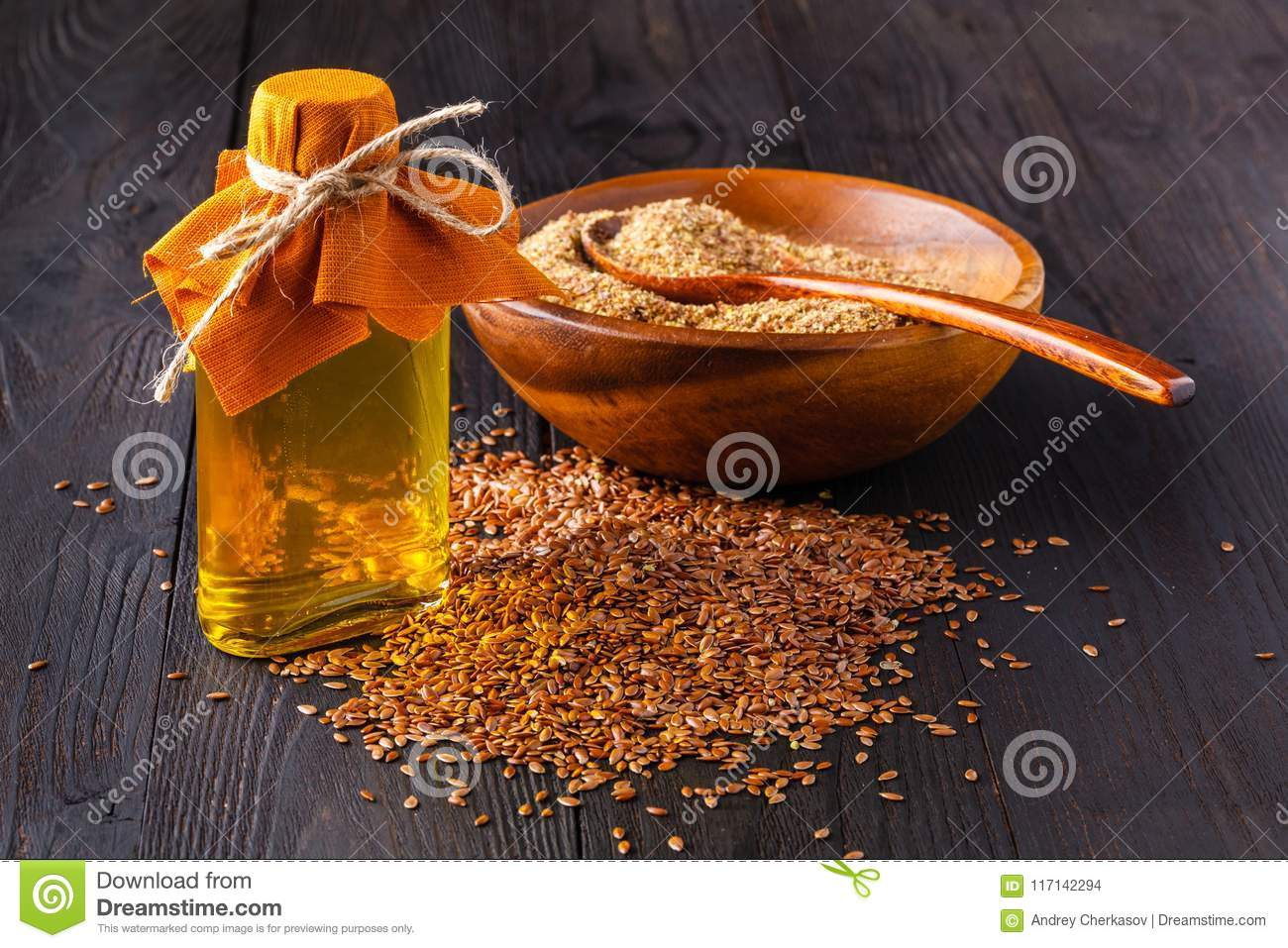 Brown Flax Seeds In Spoon And Flaxseed Oil In Glass Bottle On White