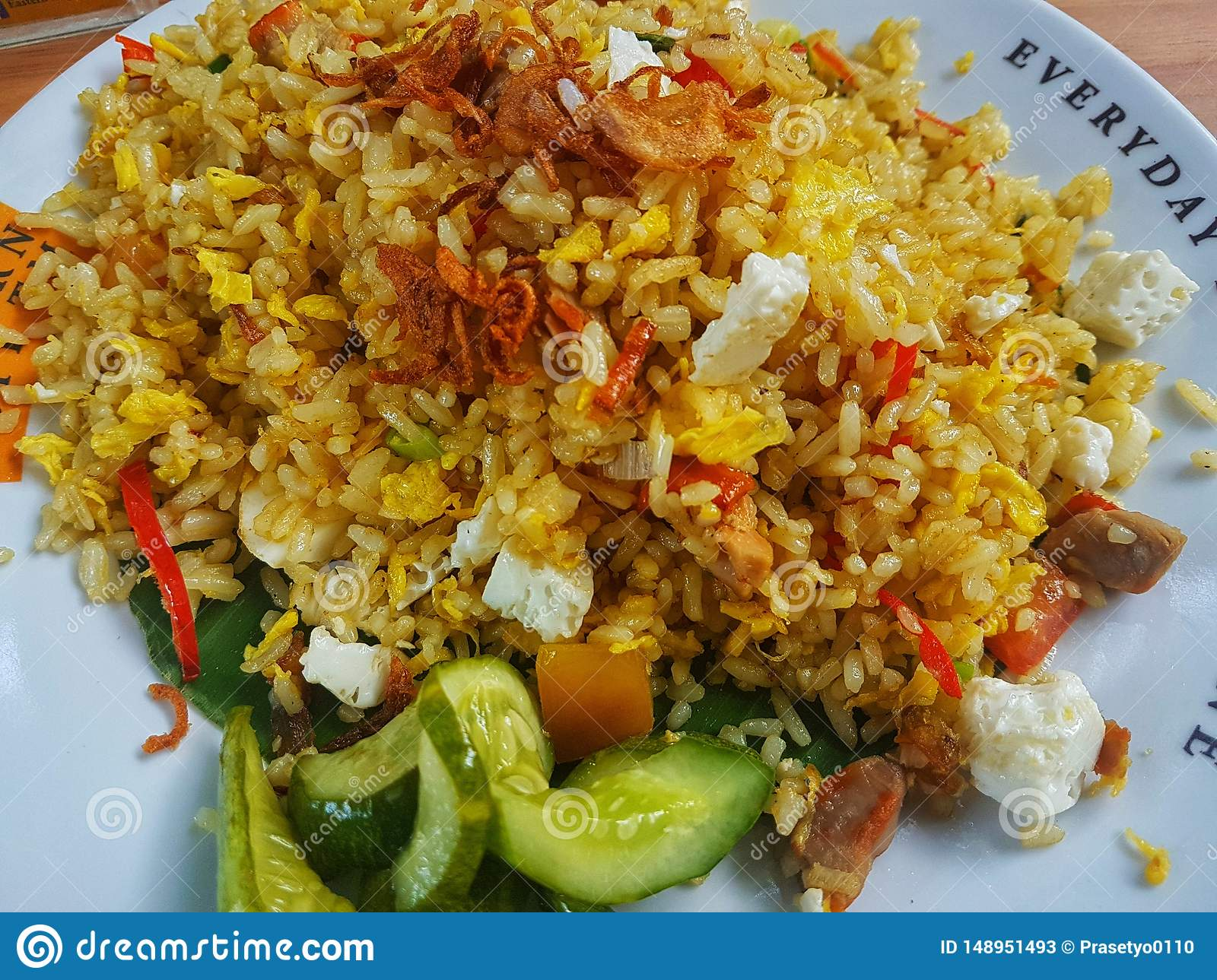 Brown fried rice with with chili,cucumber and fried onion in the white plate on the wooden table. Top view close up details.