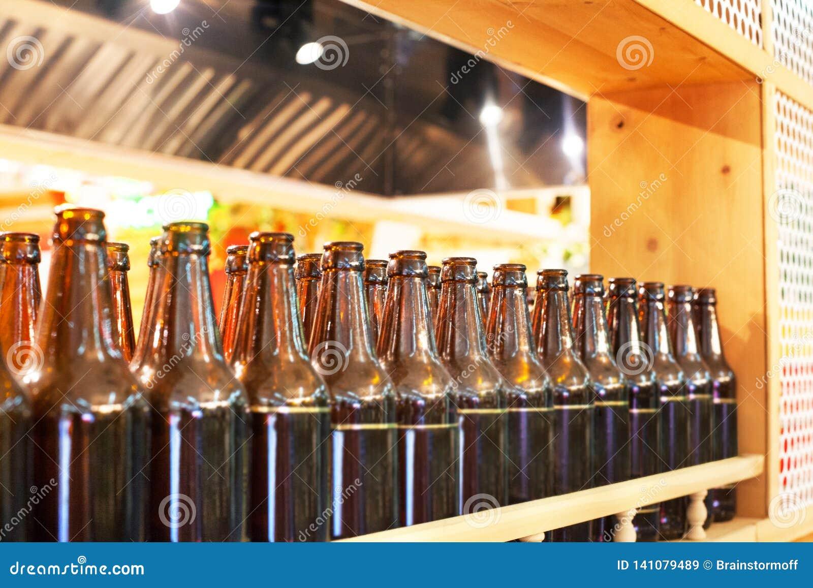 Brown-Glasflaschen Bier in der Reihe auf hölzernem Regal, Innenarchitektur der Bar, Bierprobierenkonzept, Nachtlebenart, Brauerei