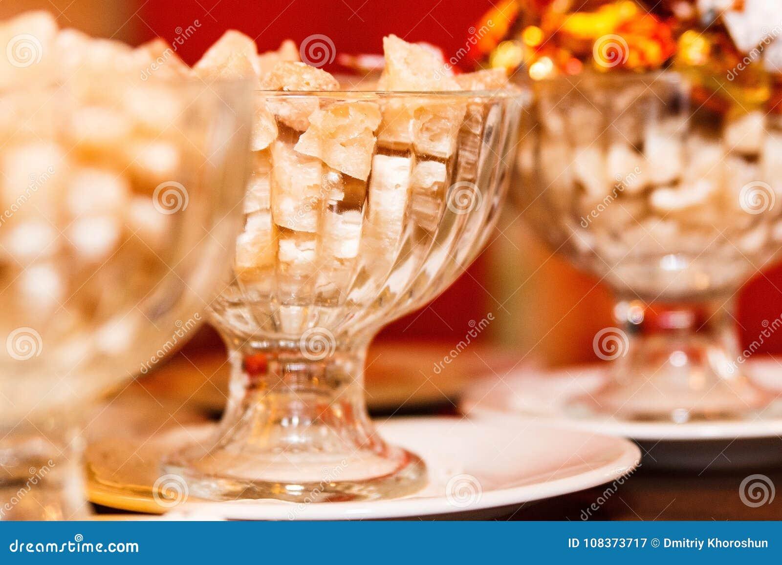 Brown gomółki cukierki w pucharach na stole i cukier, zbliżenie, selekcyjna ostrość, grżemy brzmienie