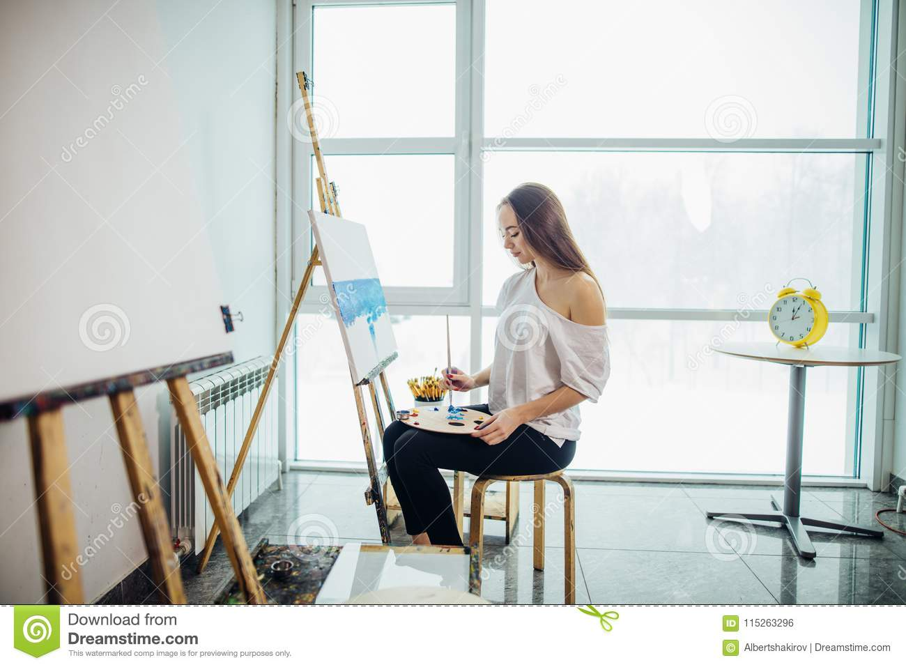 Young Painter Woman Painting On Easel In Workshop Stock