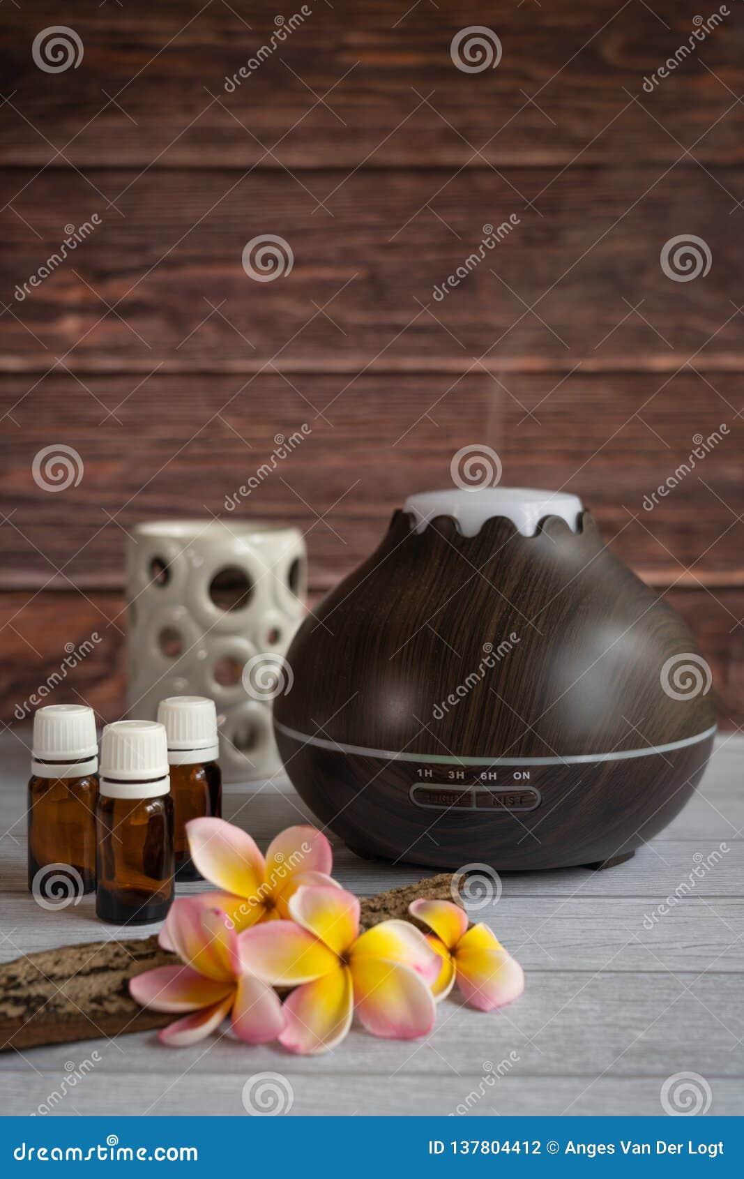 Brown istotnego oleju dyfuzor z frangipani kwiatami i świeczką,