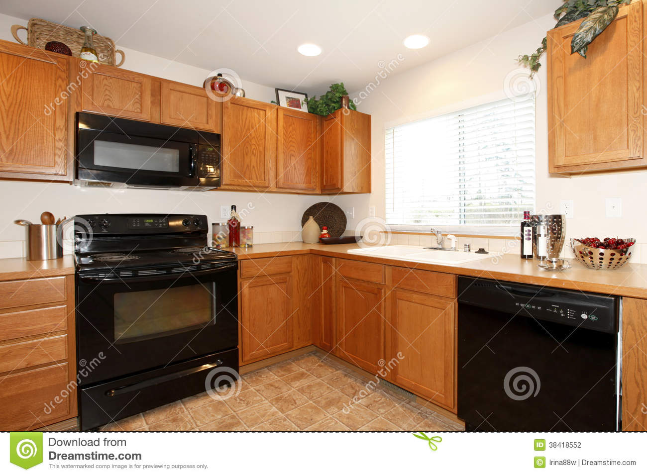 Brown kitchen cabinets with black appliances stock photo for Black and brown kitchen cabinets