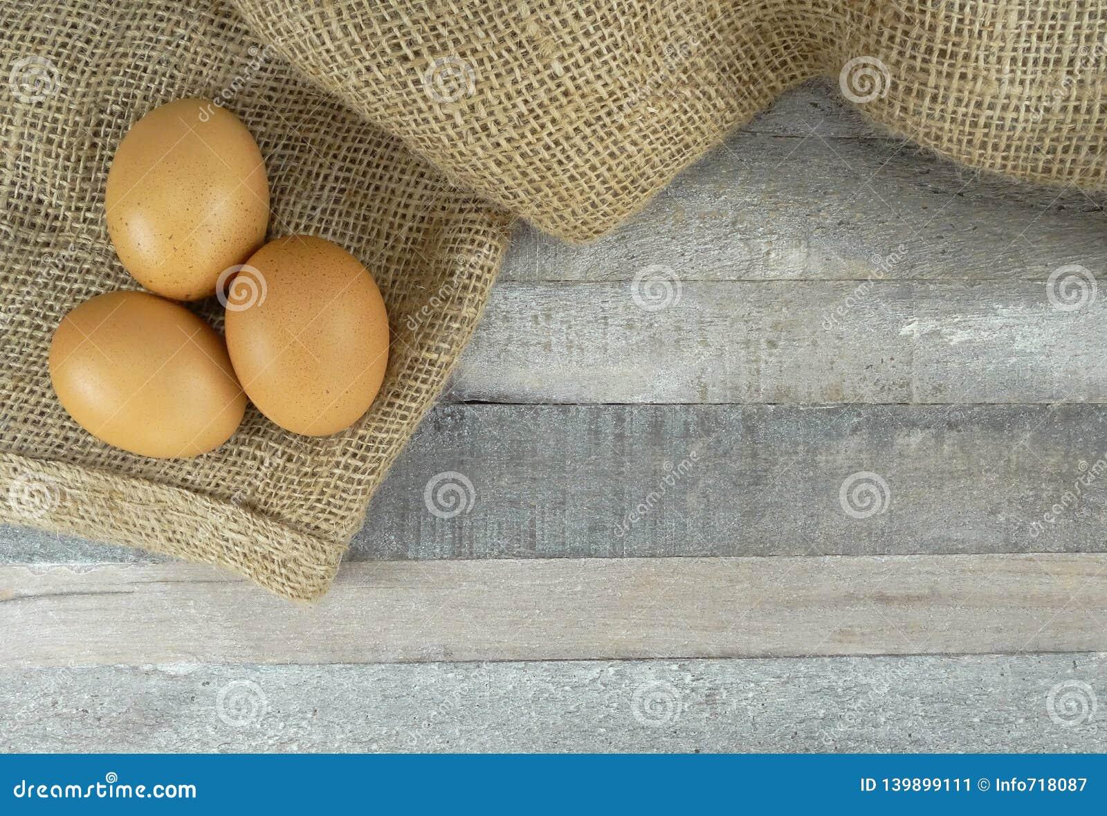 Brown kurczaka jajka na burlap nad drewnianym tłem