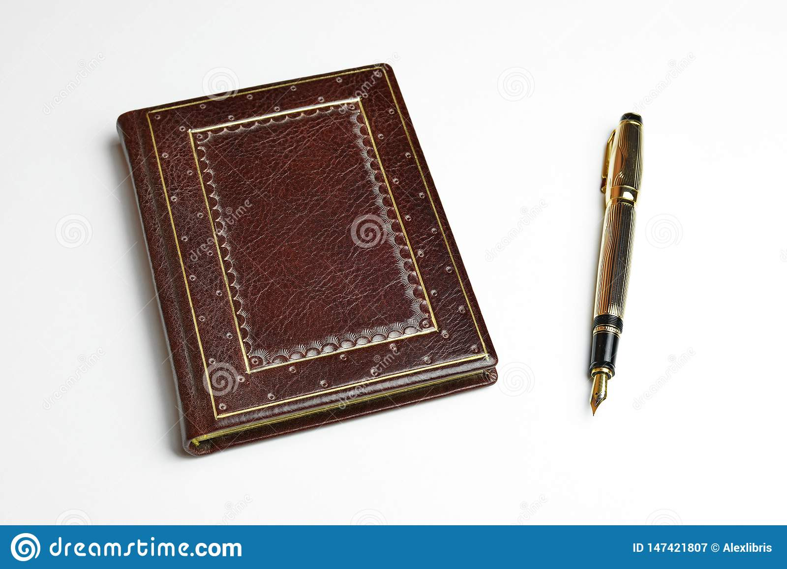 Brown leather journal with the posted golden fountain pen on the side