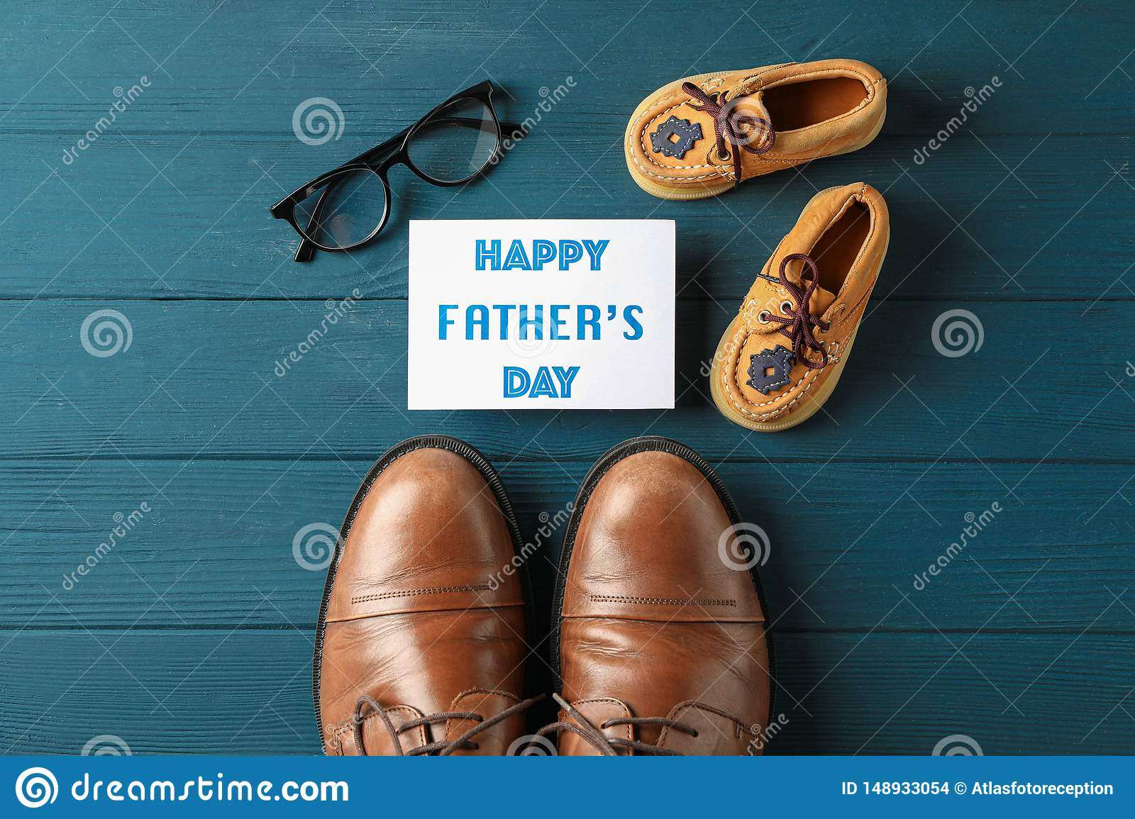 Brown leather shoes, children`s shoes, inscription happy fathers day, and glasses on wooden background