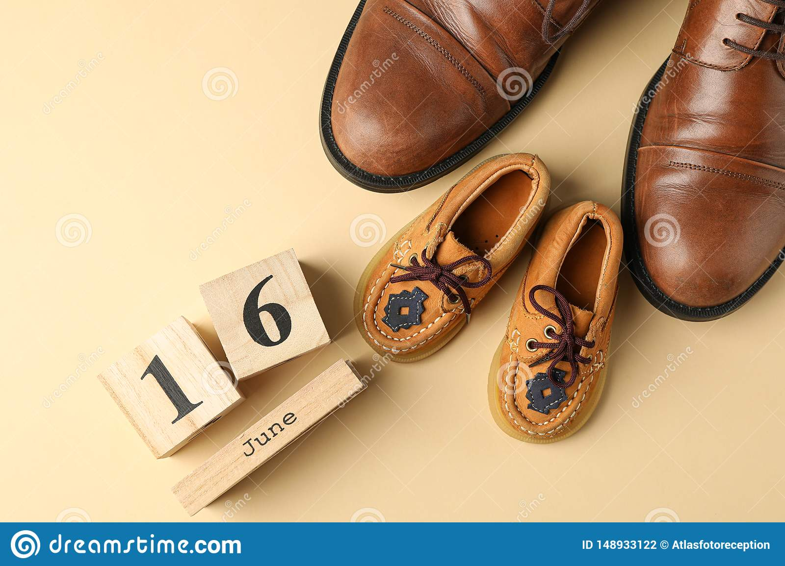 Brown leather shoes, children`s shoes and wooden calendar on color background, space for text