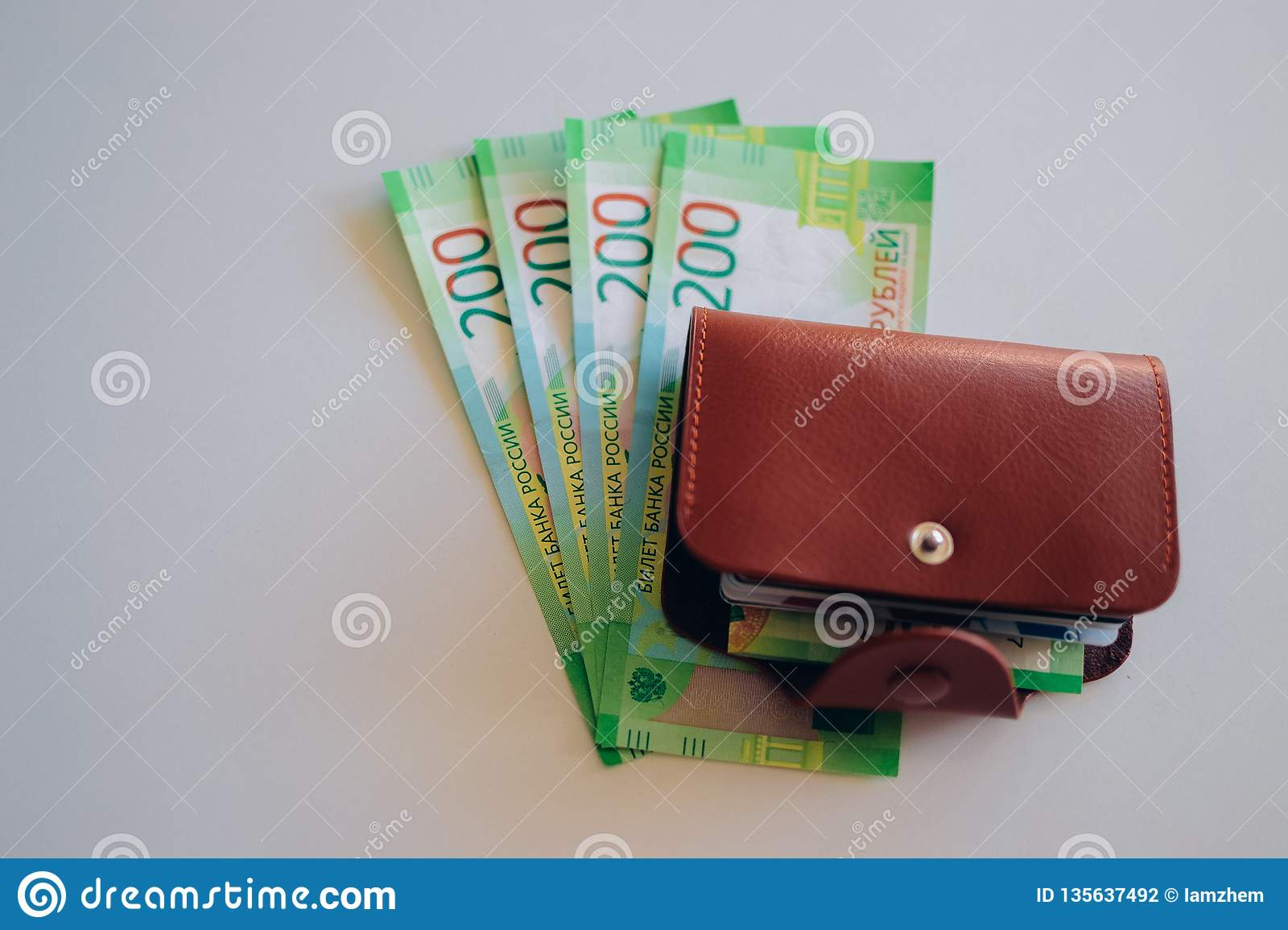 Brown leather wallet with plastic cards and Bank of Russia banknotes. Russian money for 200 rubles