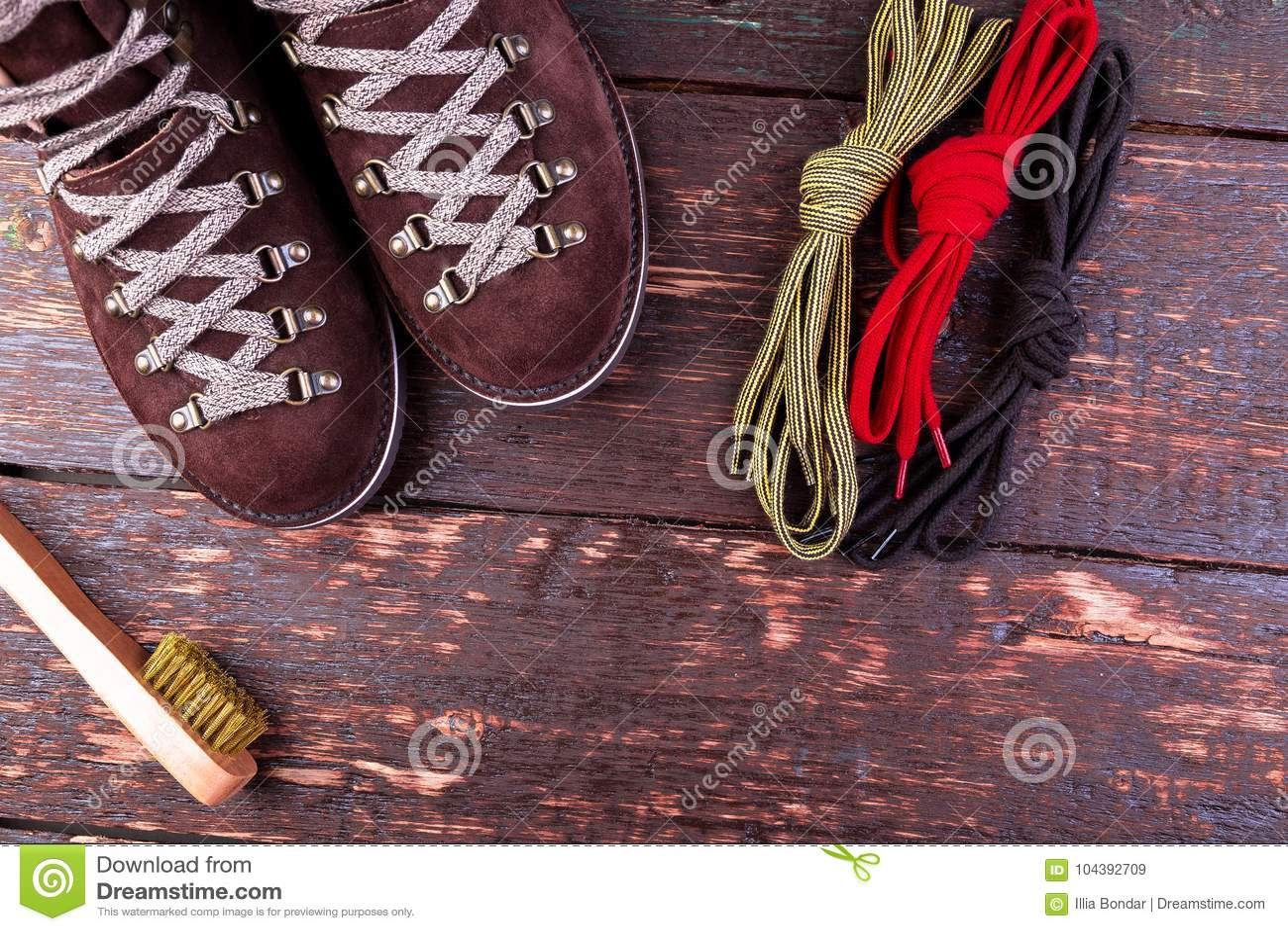 Brown mężczyzna zamszowy inicjuje z szczotkarskimi shoelaces na drewnianym tle Jesieni lub zimy buty
