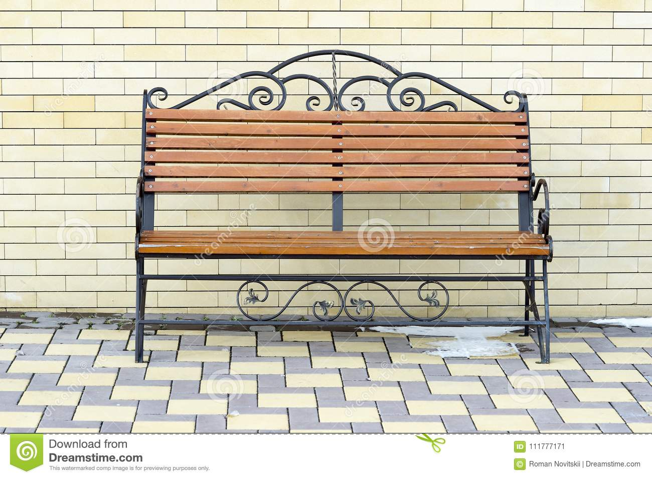 Brown Park bench against the wall of a light yellow brick.