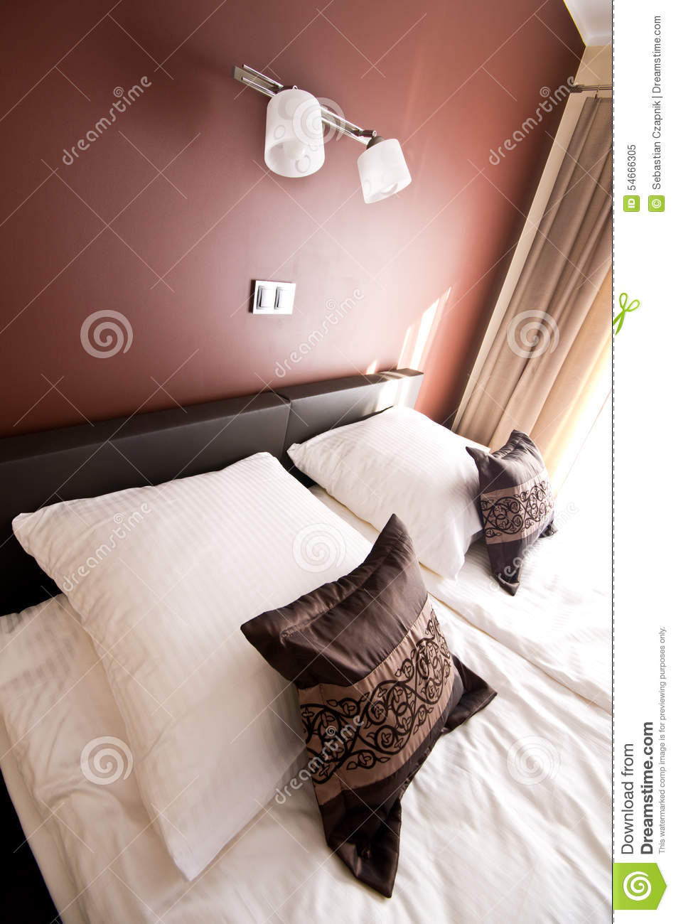 Brown pillow on bed with wall lighting stock photo image for Wall pillow for bed