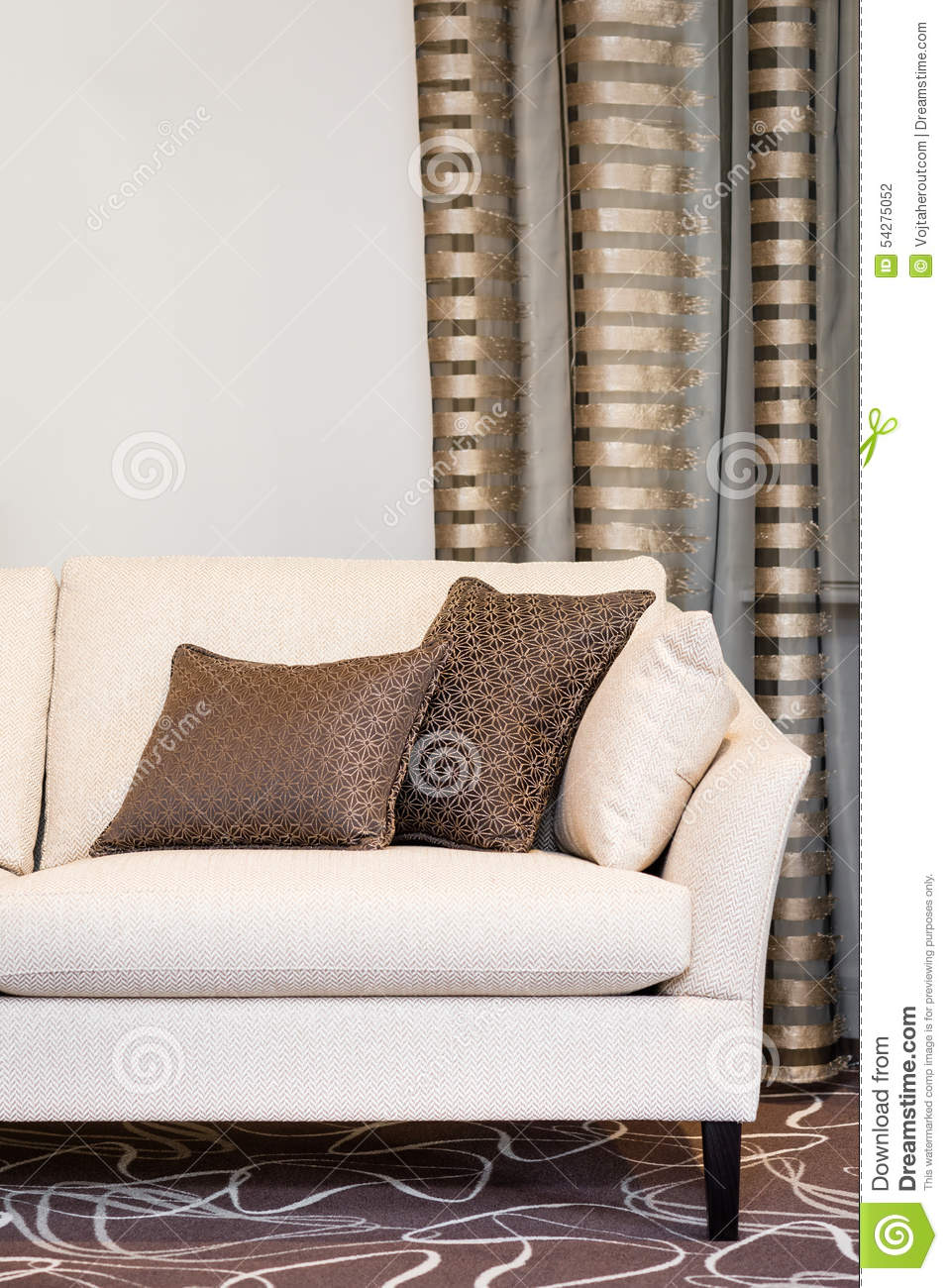 Brown Pillows On Empty Beige Sofa Stock Photo