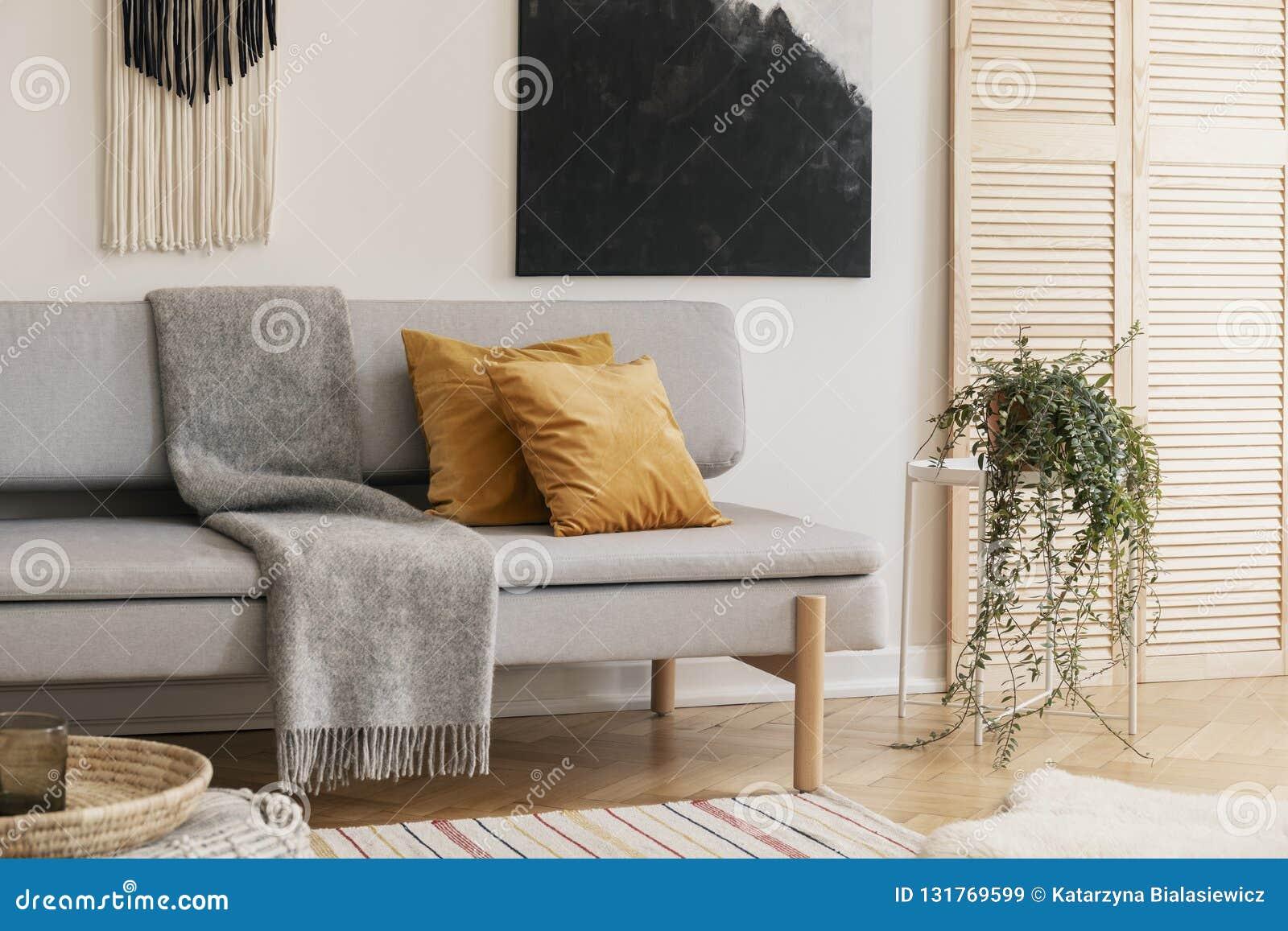 Brown poduszki i popielata koc na leżance w żywym pokoju