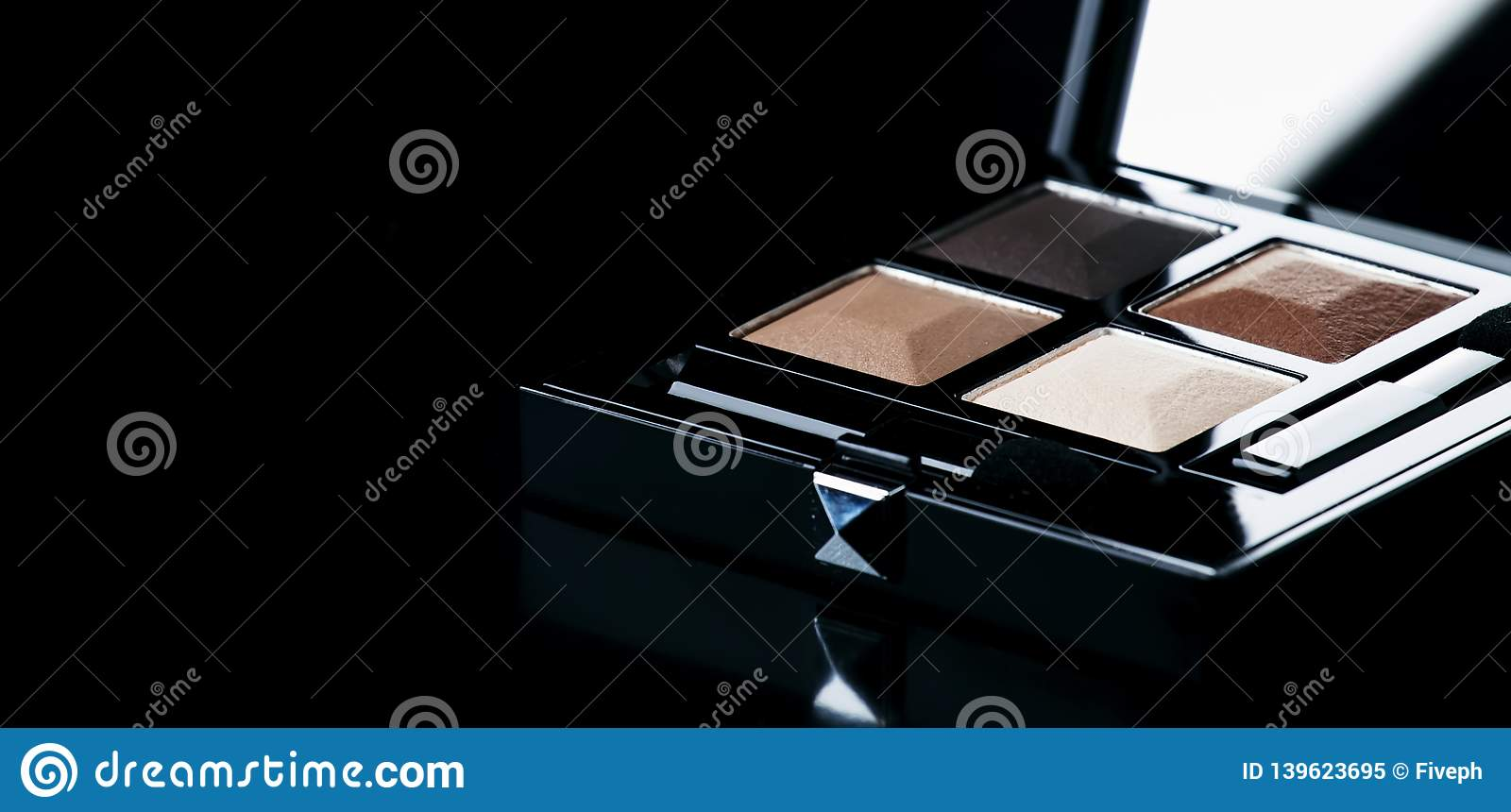 Brown sand eyeshadow in black box on glossy black background, place for text, selective focus