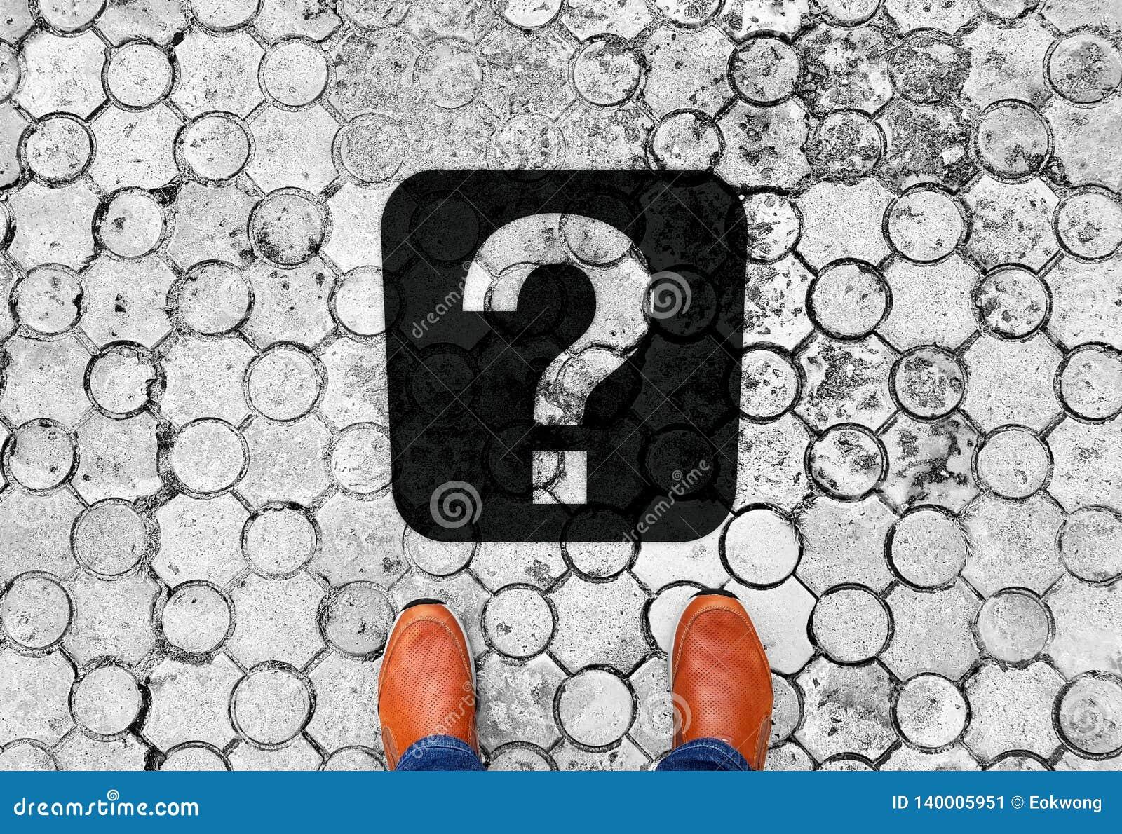 Brown-Schuhe, die auf dem Boden mit Fragezeichen - Bedeutung des lebens- folgenden Reiseziels stehen