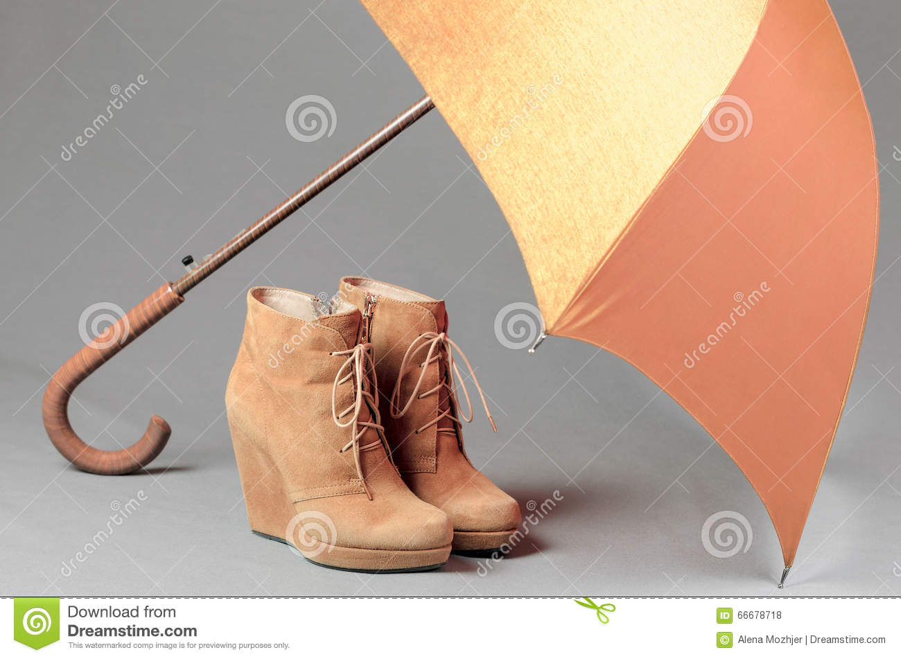 brown suede boots an umbrella on a gray background