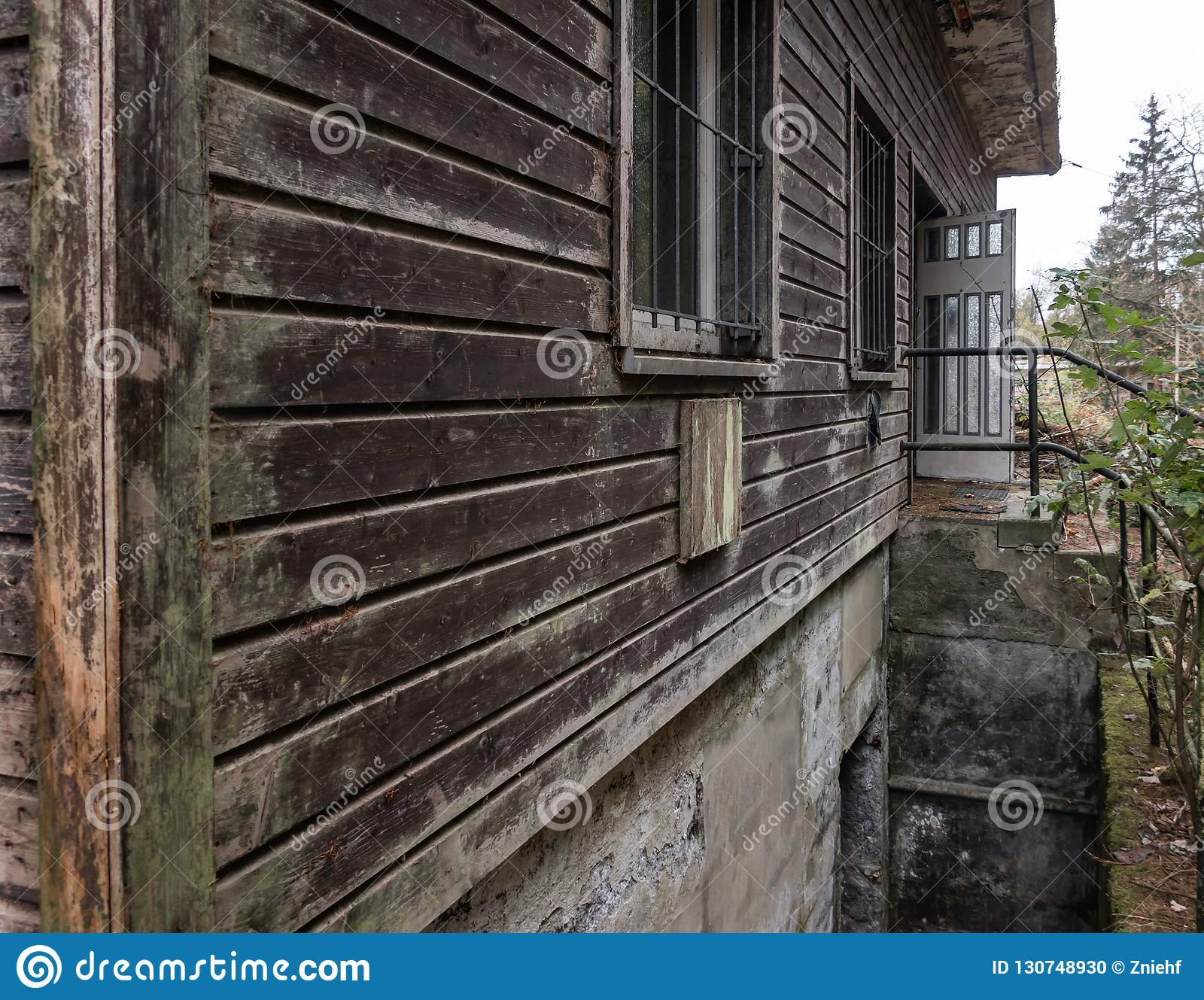 Brown weathered facade of an old abandoned wooden house in the mountains, close-up view from the house corner.